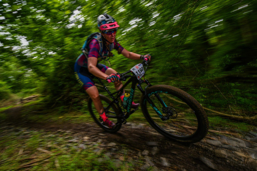 Woman in a high-speed mountain bike race, leaning through a turn