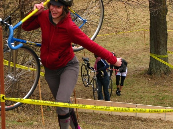 woman walks up a grass hill on a cyclocross course with a fixed gear bike on her shoulder